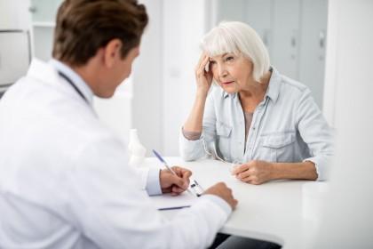 Eine Seniorin sitzt im Behandlungszimmer einer Arztpraxis. Ihr gegenüber sitzt ein Arzt im Gespräch der mitschreibt. Die Seniorin fässt sich während des Gesprächs mit der rechten Hand an die Schläfe.