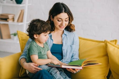 Eine Mutter hat ihr etwa zwei jähriges Kind auf dem Schoß. Beide sitzen auf dem Sofa und schauen sich ein Buch an.