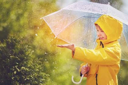 Ein Junge mit Regenschirm und gelben Regenmantel genießt den Regen
