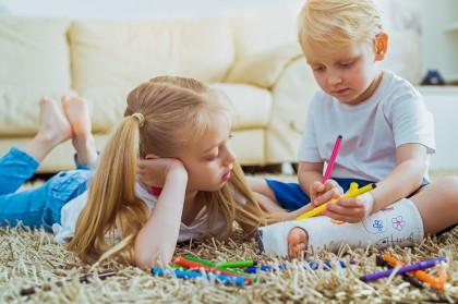 Zwei Kinder sitzen auf einem Teppich und malen. Der Junge hat einen eingegipsten Fuß.