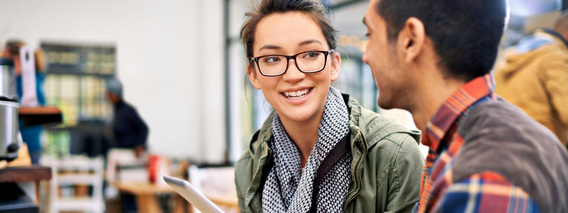 Eine junge Frau mit Brille und grüner Jacke unterhält sich mit einem jungen Mann mit kariertem Hemd. Beide lächeln sich an und halten ein Tablet in der Hand.