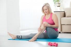 Eine etwa 60 jährige Frau sitzt im Wohnzimmer auf einer Sportmatte und umfasst ihre linke Wade und Schienbein. Vor ihr liegen zwei kleine Hanteln.