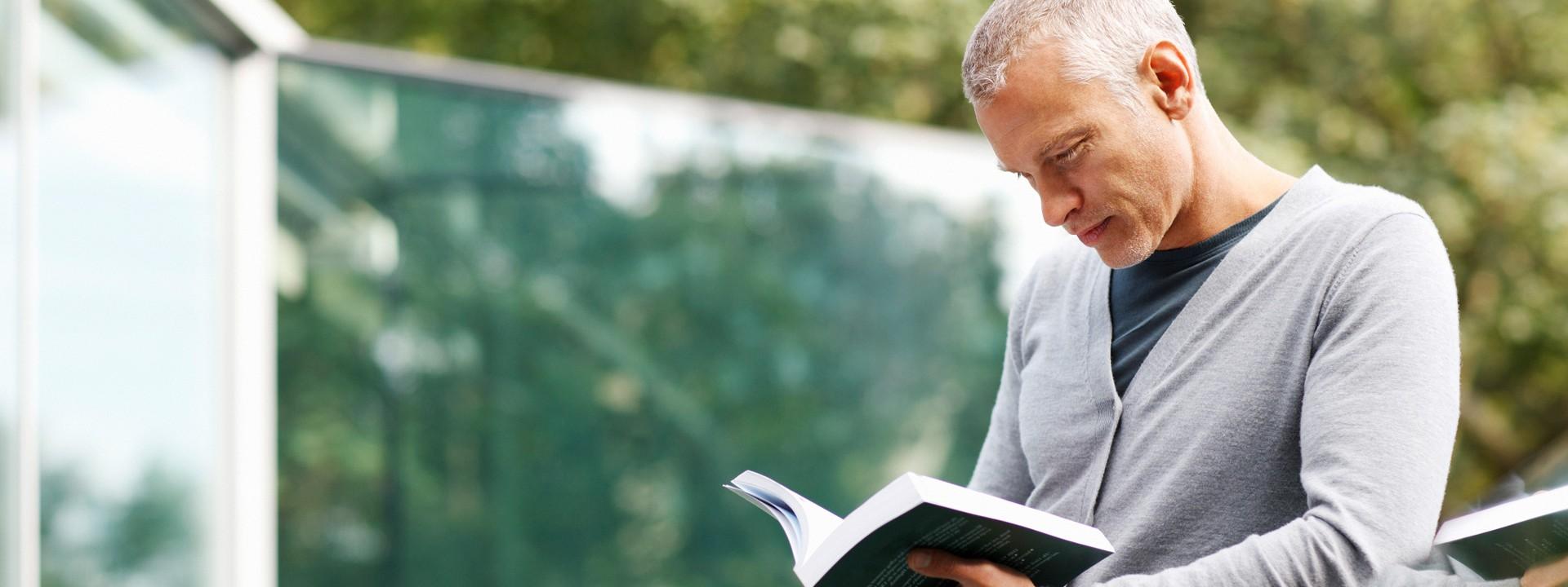 Ein Mann steht an einem Geländer und liest ein Buch.