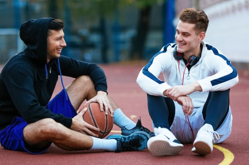 Zwei circa 20-Jährige Männer unterhalten sich sitzend auf einem Sportplatz.