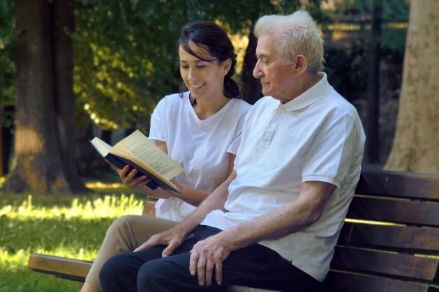 Eine Altenpflegerin sitzt mit einem Senior auf einer Bank in der Natur. Sie liest ihm etwas in einem Buch vor und beide lächeln.