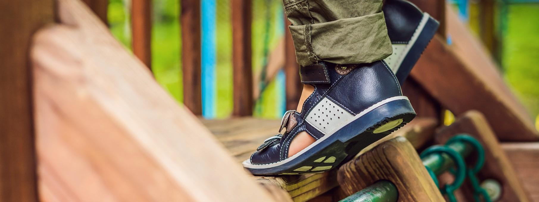 Ein Kind klettert auf einem Spielplatz und trägt orthopädische Schuhe.