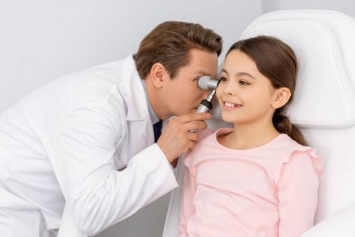 Ein etwa 10 jähriges Mädchen wird von einem Arzt am rechten Ohr untersucht.