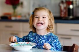 Ein etwa 3-jähriges Mädchen sitzt mit einem Teller am Tisch und streckt die Zunge raus.
