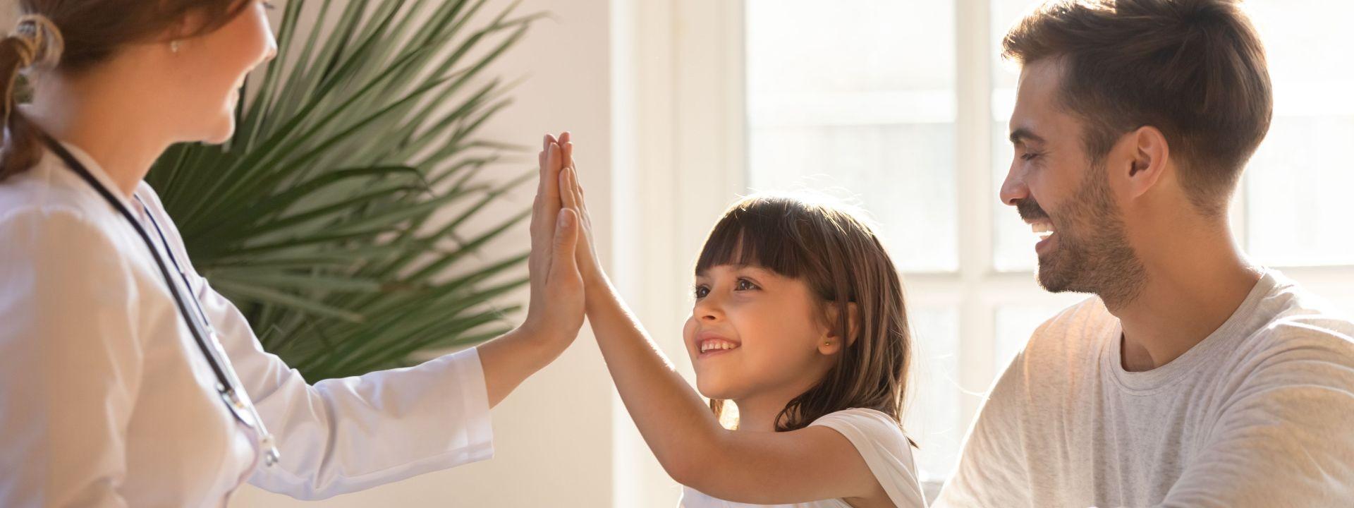 Ein etwa 6 jähriges Mädchen gibt einer Ärztin ein High-Five. Ihr Vater sitzt daneben. Alle drei lachen.