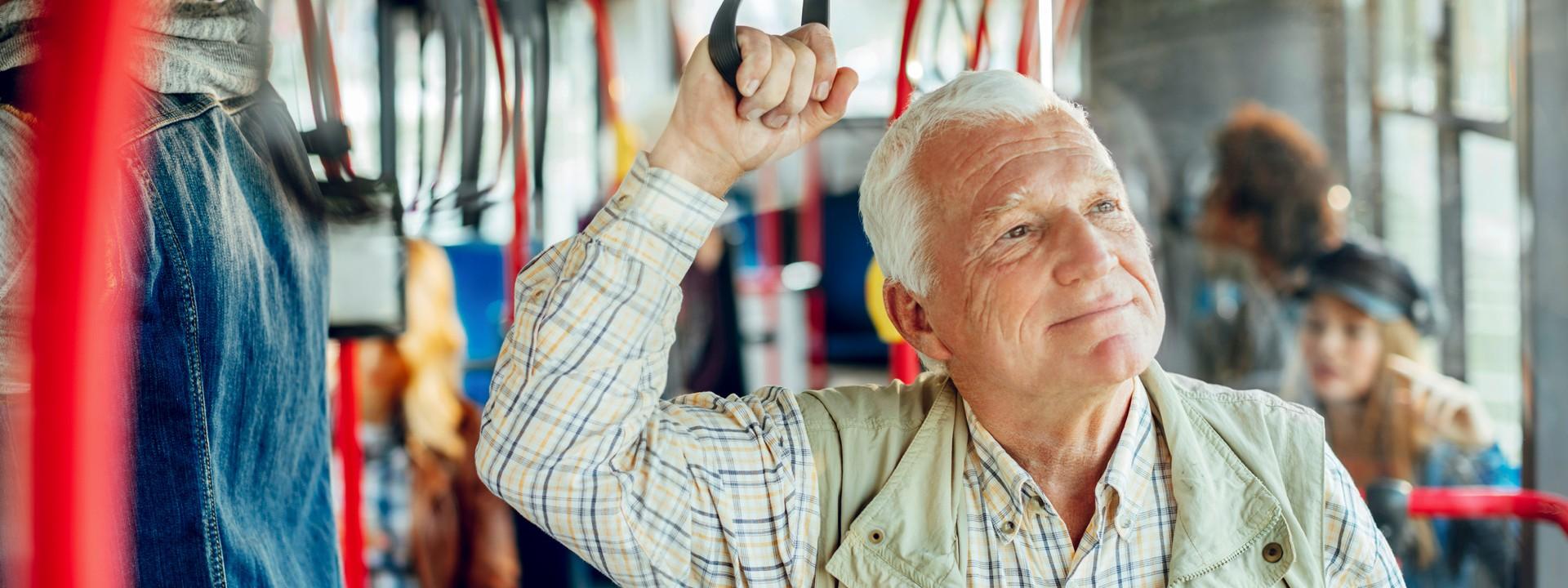 Ein etwa 70-jähriger Mann hält sich in einer Straßenbahn an einer Halteschlaufe fest.