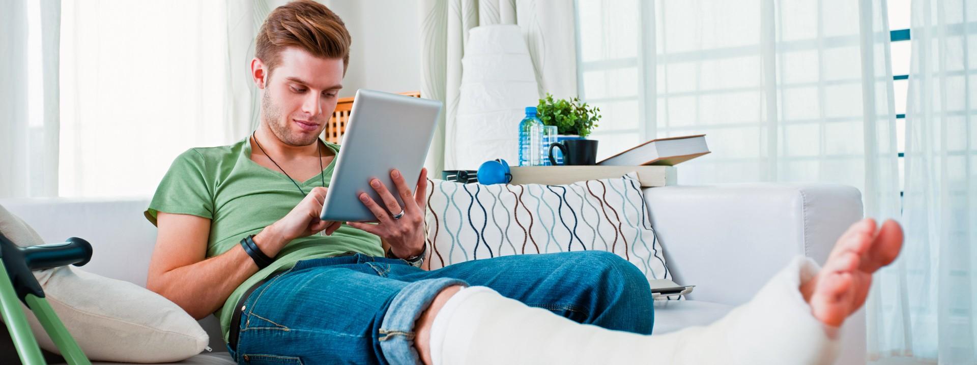Ein junger Mann sitzt mit gebrochenem Bein auf dem Sofa und hat ein Tablet in der Hand.