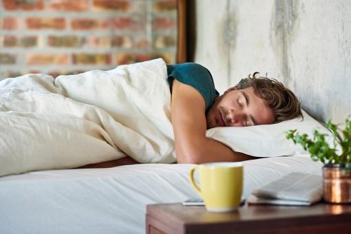 Mann liegt schlafend im Bett.