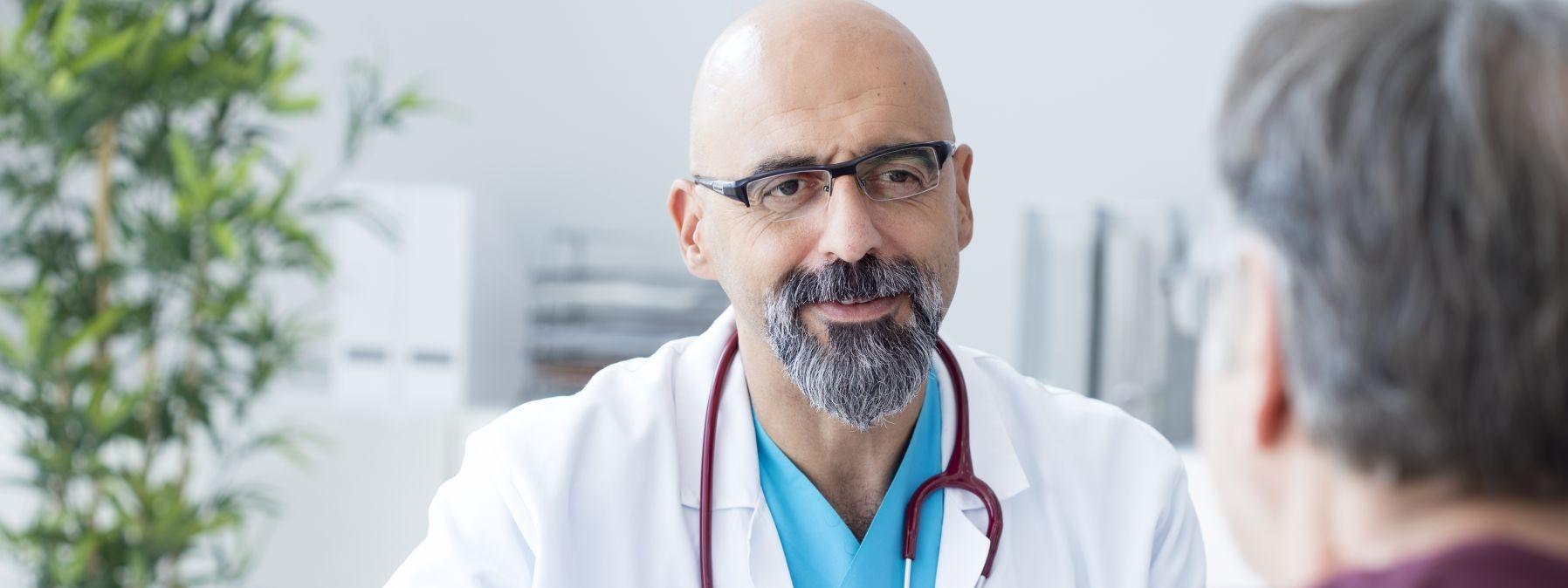 Ein Arzt trägt ein Stethoskop um den Hals und berät in seiner Praxis einen männlichen Patienten.