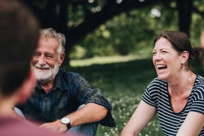 Eine Gruppe von Leuten sitzen im park und unterhalten sich. Alle lachen ausgiebig.