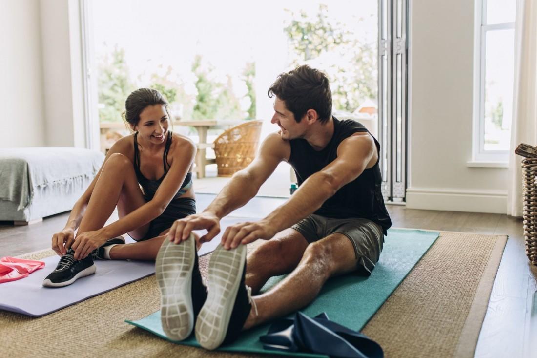 Eine etwa 25 jähriger Frau un ein etwa 25 jähriger Mann sitzen in einem Wohnzimmer auf Yogamatten. Die Frau bindet ihren Sportschuh und der Mann dehnt seine Beine. Beide lächeln sich an und sind verschwitzt.