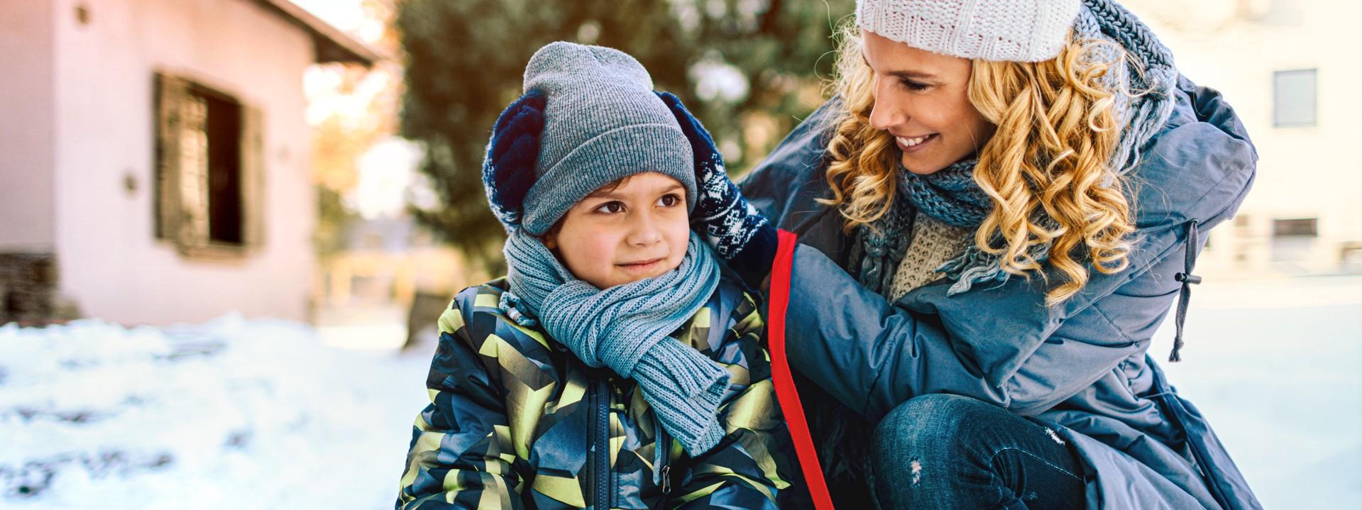 Eine circa 35jährige Frau setzt ihrem circa 8jährigem Sohn eine Mütze auf. Er sitzt dabei vor dem Haus auf seinem Schlitten im Schnee. Sie hockt daneben.
