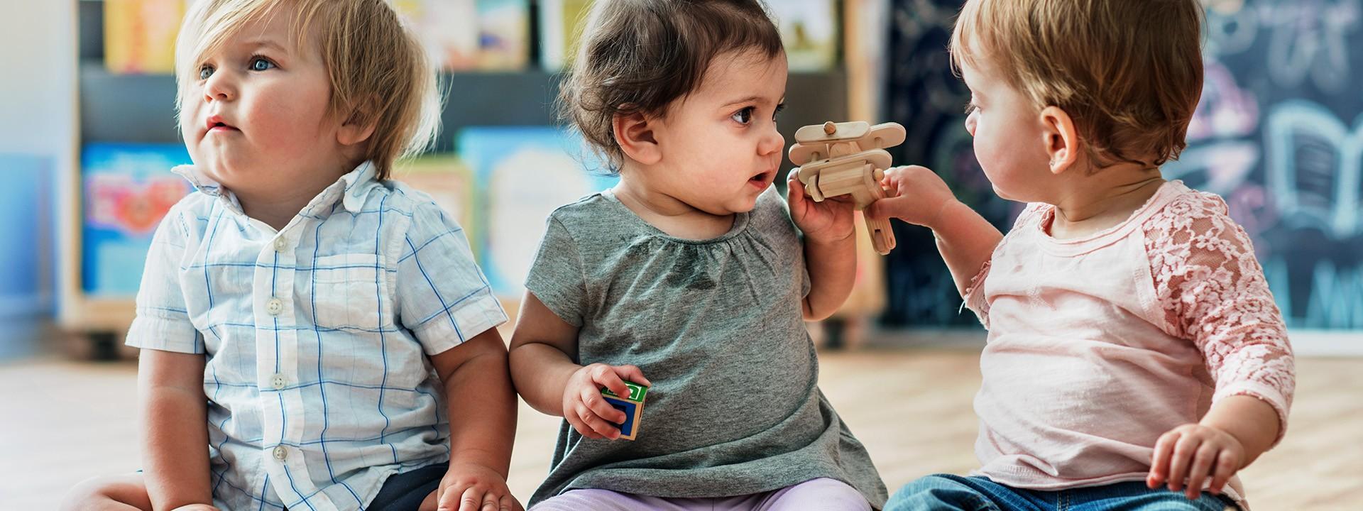 Drei Babys sitzen zusammen und spielen mit bunten Bausteinen.
