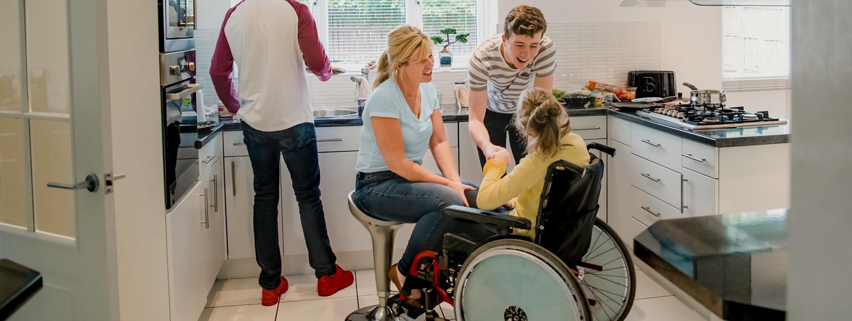 Familie einer Rollstuhlfahrerin in der Küche