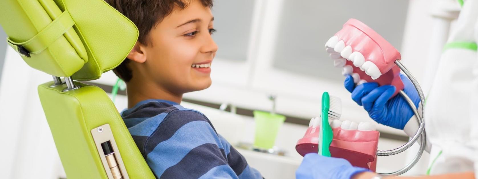 Ein etwa 7 jähriger Junge sitzt auf einem Behandlungsstuhl beim Zahnarzt. Die Zahnärztin zeigt ihm anhand eines Gebiss wie man die Zähne putzt,