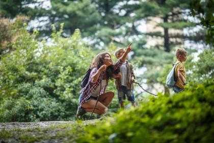 Eine etwa 35 jährige Frau wandert mit zwei etwa 7 Jahre alten Jungs durch die Natur. Sie hat sich zu einem Jungen herunter gehockt und deutet auf etwas mit ihrem Finger. Der Junge schaut aufmerksam zu.