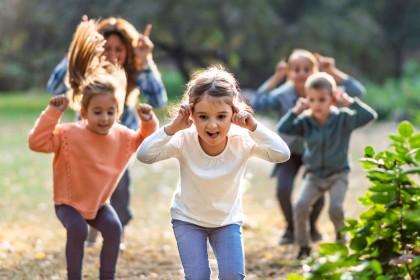 Kinder spielen im Freien, greifen sich an die Ohren und hüpfen dabei.