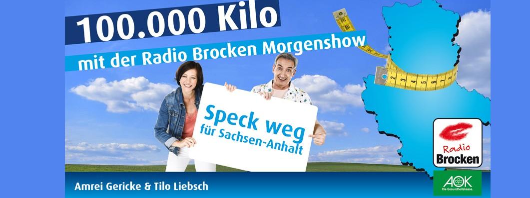 """Die Radiomoderatoren von Radio Brocken Amrei Gericke und Tilo Liebsch halten ein Plakat auf dem steht """"Speck weg für Sachsen-Anhalt"""". Auf der rechten Seite des Bildes ist der Umriss von Sachsen-Anhalt und drum herum ein Maßband."""