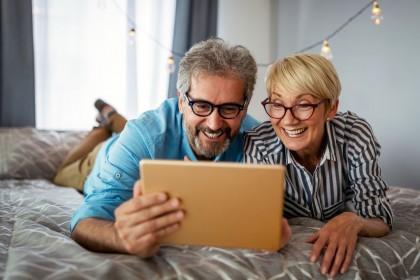 Ein etwa 55 jähriges Pärchen liegt auf einem Bett. Sie schauen gemeinsam auf ein Tablet und lachen.