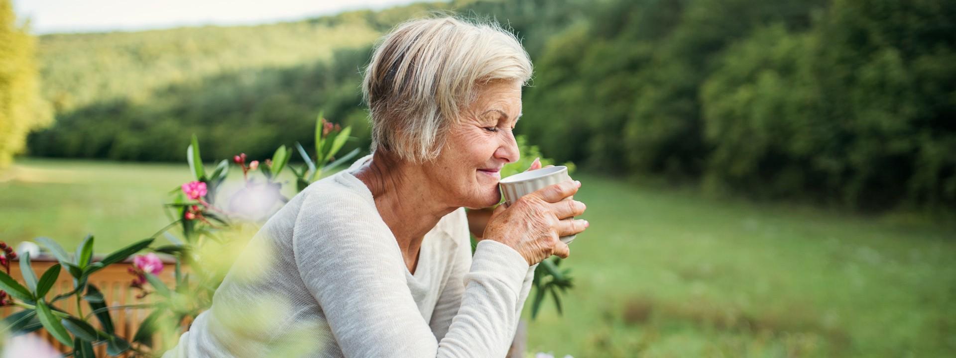 Eine Seniorin steht an einen Zaun gelehnt und trinkt eine Tasse Tee. Sie schaut in die Natur und lächelt.