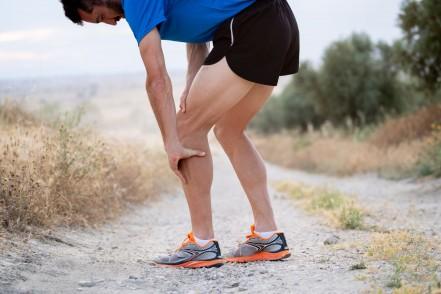 Ein Mann in Sportkleidung steht auf einer unasphaltierten Straße und umfasst sein linkes Bein.