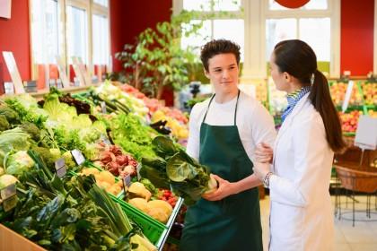 Ein etwa 16 jähriger Junge arbeitet in der Gemüseabteilung in einem Einkaufsladen. Dabei hält er einen Salatkopf und unterhält sich mit der Marktleiterin.
