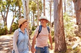 Ein etwa 55 jähriges Paar läuft hand ind Hand durch einen Wald. Beide lächeln sich an.