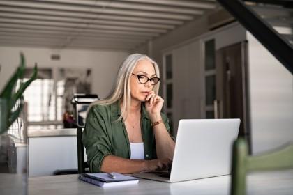 Eine etwa 60 jährige Frau sitzt an einem Tisch und arbeitet an einem Laptop. Neben ihr liegen ihre Notizen.