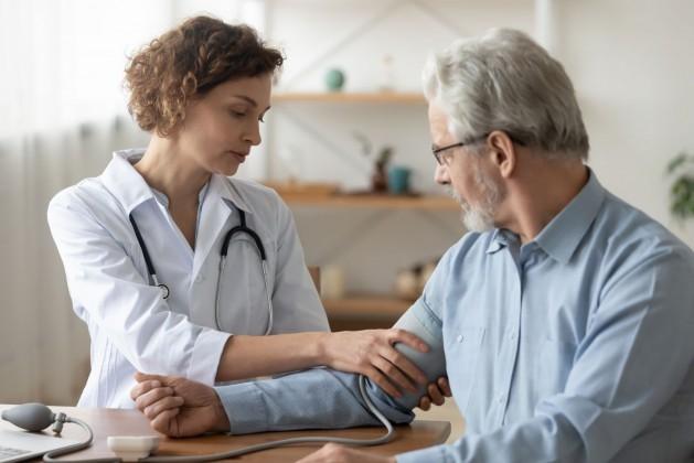Ein etwa 60 jähriger Mann lässt sich von einer Ärztin am rechten Arm den Blutdruck messen.