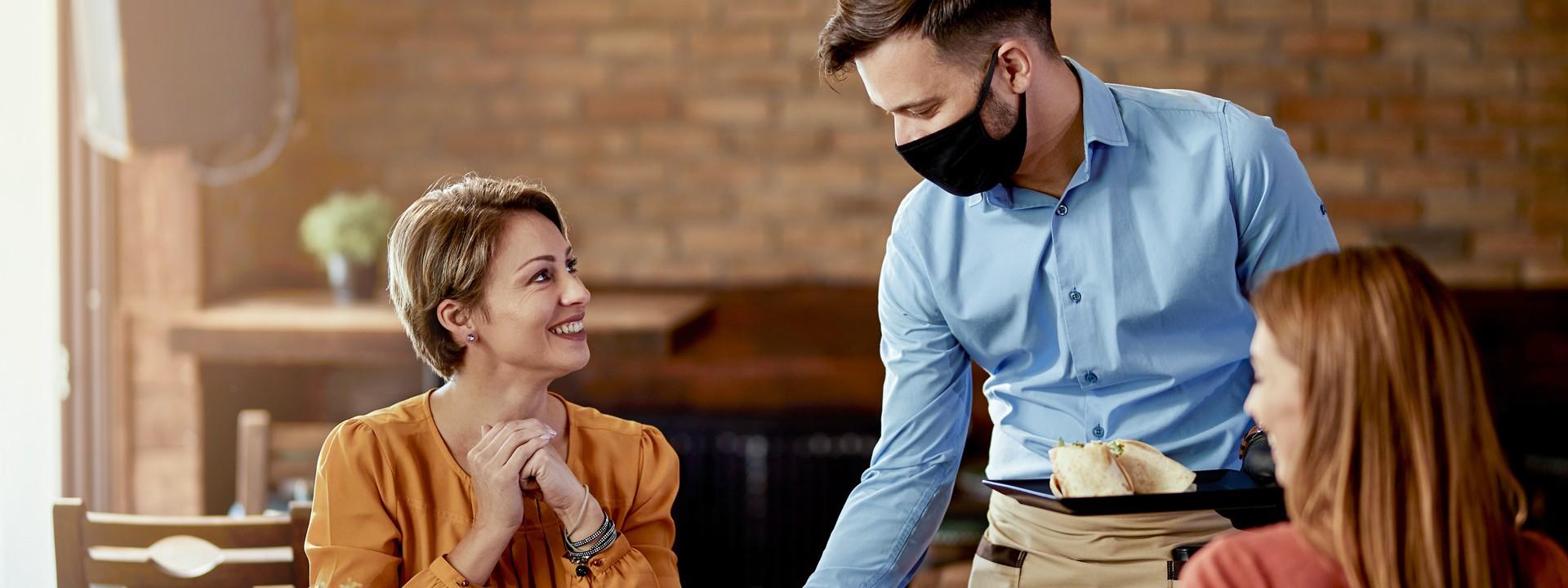 2 Frauen und Kellner mit Maske in Cafe