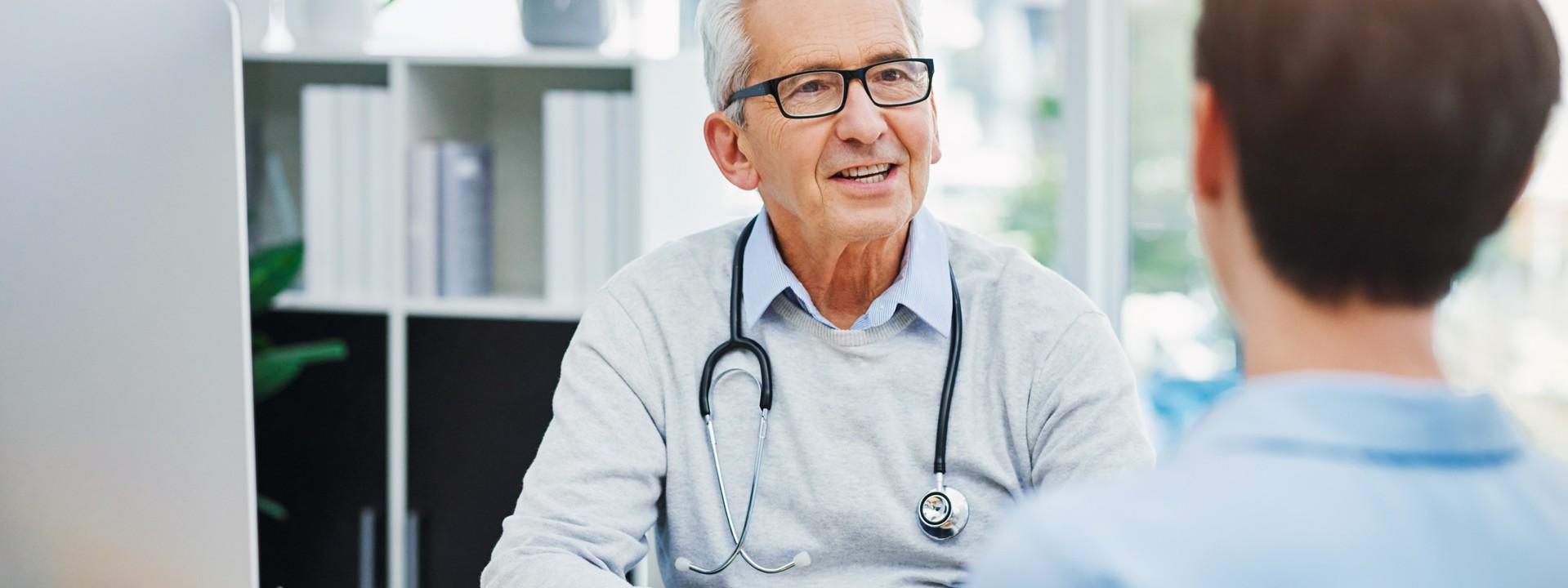 Ein etwas 60 jähriger Arzt sitzt an einem Schreibtisch und berät einen etwas 30 jährigen Patienten.