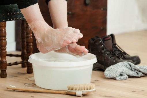 Zwei Füße werden in einer Schüssel ausgiebig gebadet. Daneben stehen Wanderschuhe. Vor der Schüssel liegt eine Holzbürste.