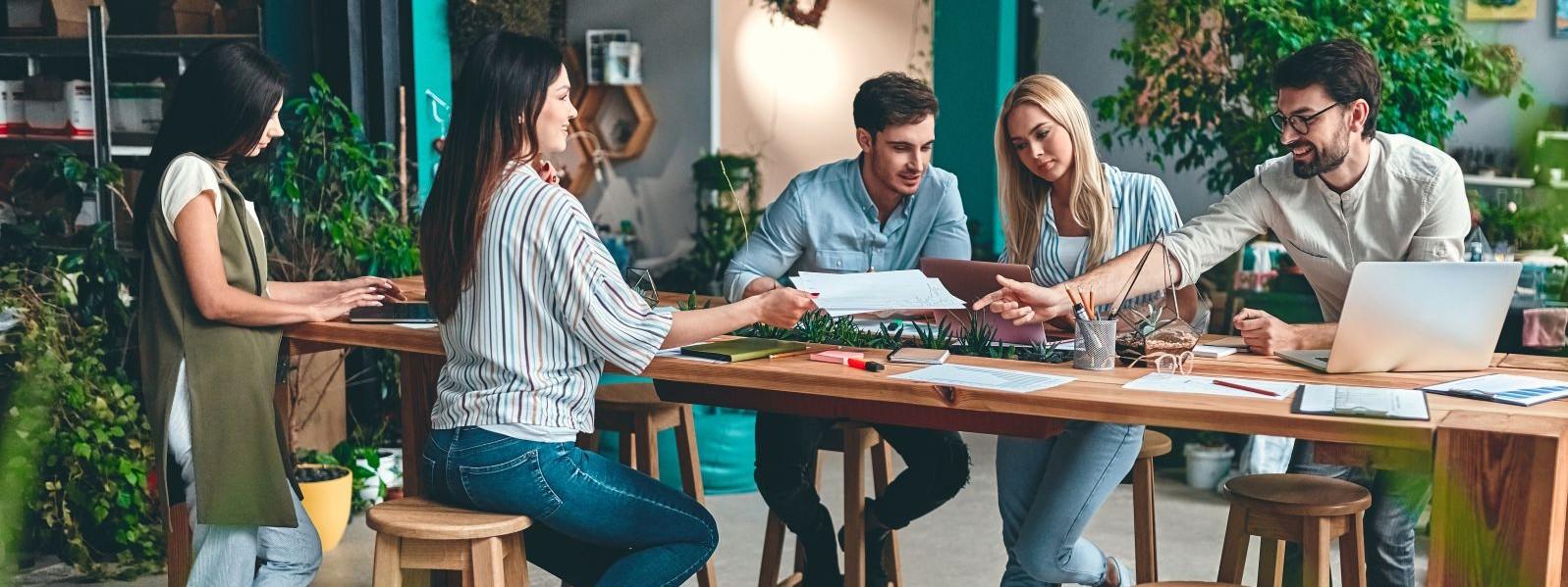 Eine Gruppe von etwa 30 jährigen Personen sitzt an einem großen Holztisch in einer grünen Firma. Alle diskutieren angeregt.