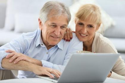 Ein älteres Pärchen sitzt an einem Tisch und schaut gemeinsam auf einen Laptop. Beide lächeln.