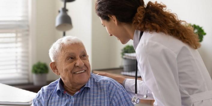 Ein Senior sitzt in einem Behandlungszimmer. Von ihm seitlich steht eine Ärztin, die seine Hand hält. Beide schauen sich an und lächeln ausgiebig.