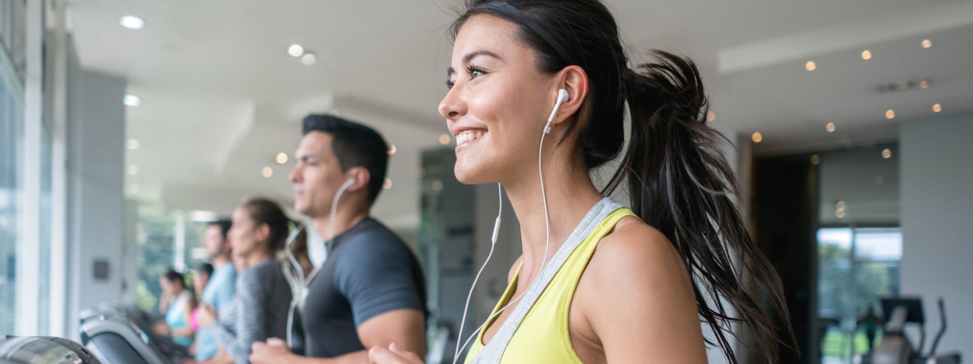 Eine etwa 30-jährige Frau läuft zusammen mit anderen Personen auf einem Laufband im Fitnessstudio.